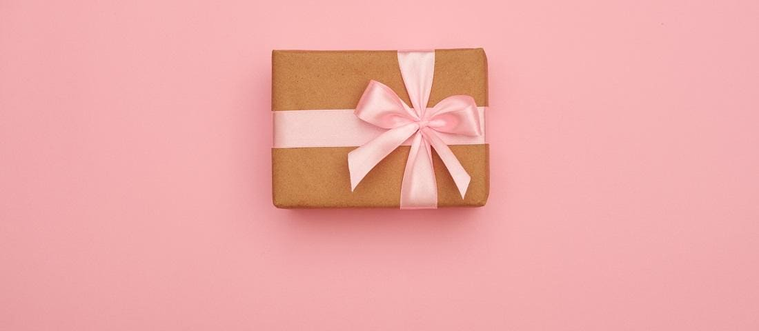 Present box with pink bow placed in the middle